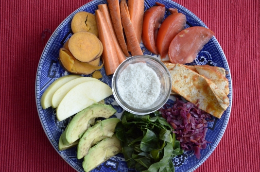 Tomato, carrots, yam, apple, avocado, collards, purple kraut, tofu with tomato sauce, and sea salt in the center.