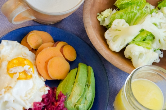 two farm eggs sunny-side with ghee, steamed sweet potato, ruby kraut with carrots, avocado, steamed cauliflower, romaine with olive oil and nutritional yeast drink.